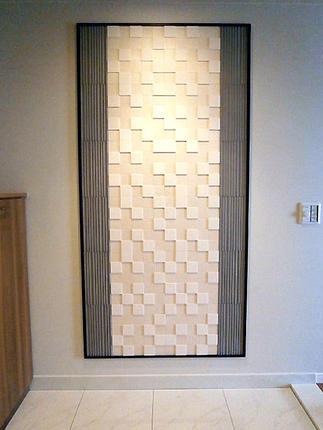 玄関はアートを飾るように陰影が美しいレリーフタイルを飾って